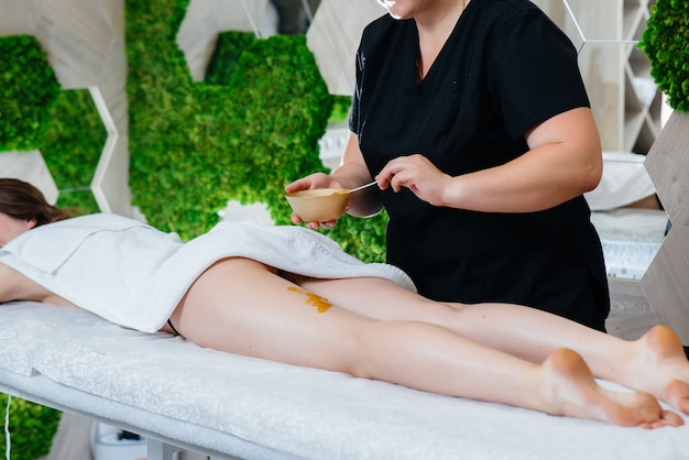 Una giovane ragazza carina si sta godendo un massaggio professionale con miele presso la spa