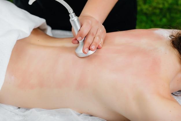 Una giovane ragazza carina si sta godendo un massaggio professionale sottovuoto presso la spa. cura del corpo. salone di bellezza.