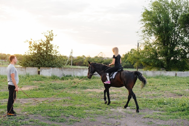 Una ragazza giovane e carina sta imparando a cavalcare una cavalla purosangue in un giorno d'estate al ranch