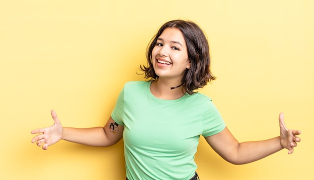 Giovane ragazza carina che sembra felice, arrogante, orgogliosa e soddisfatta di sé, sentendosi una numero uno