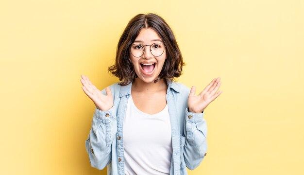 Giovane ragazza carina che sembra felice ed eccitata, scioccata da una sorpresa inaspettata con entrambe le mani aperte accanto al viso
