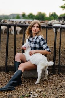 Una giovane ragazza carina pone in un ranch con capre e altri animali. agricoltura, allevamento.