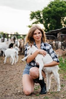Una giovane ragazza carina posa in un ranch con capre e altri animali. agricoltura, allevamento di bestiame.