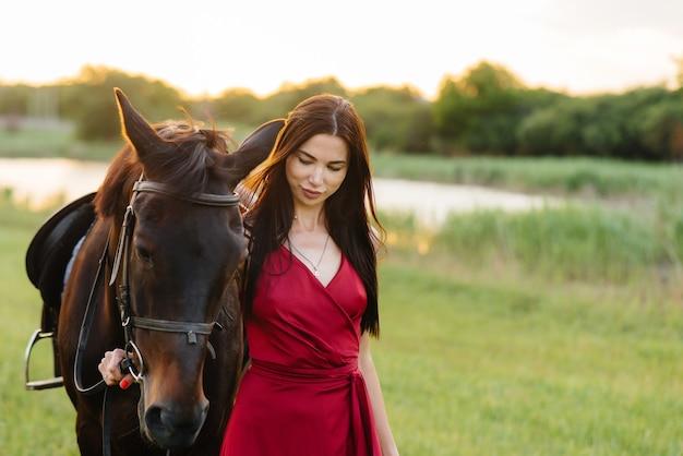 Una giovane ragazza graziosa in un vestito rosso posa in un ranch con uno stallone purosangue al tramonto. amore e cura per gli animali.