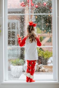 Giovane bella ragazza in pigiama di natale rosso e bianco