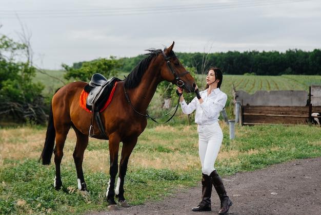 Un cavaliere giovane e grazioso posa vicino a uno stallone purosangue in un ranch. passeggiate a cavallo, corse di cavalli.