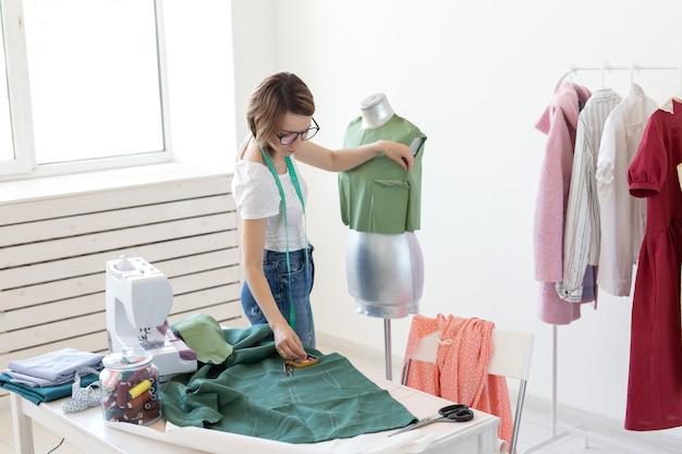 Il progettista della sarta della giovane ragazza graziosa con gli occhiali e un metro a nastro fa un nuovo prodotto con l'aiuto di un panno verde e di un manichino del sarto. concetto di laboratorio di cucito.