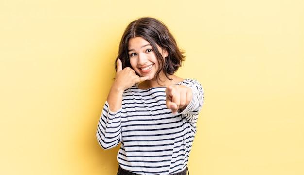 Giovane bella ragazza che sorride allegramente e indica la telecamera mentre fa una chiamata dopo un gesto, parlando al telefono