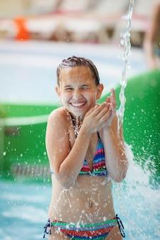 La giovane ragazza graziosa in un costume da bagno variopinto a strisce ride, sta sotto una cascata in un parco acquatico.