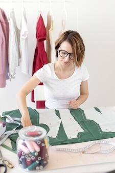 Una giovane studentessa carina studia presso uno stilista al college e fa la sua prima tesi seduto a una scrivania con una macchina da cucire. concetto di design di abbigliamento.