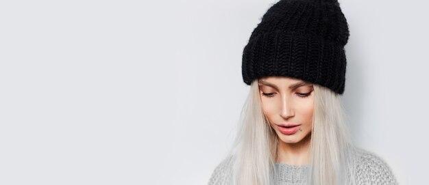 Giovane bella ragazza con capelli biondi che indossa cappello nero e maglione grigio su bianco