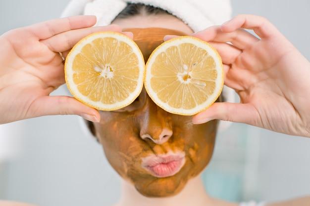 Giovane ragazza graziosa con la maschera di fango marrone sul viso che tiene le metà della frutta del limone, coprendo gli occhi. ragazza teenager che si prende cura della sua pelle. trattamento di bellezza.
