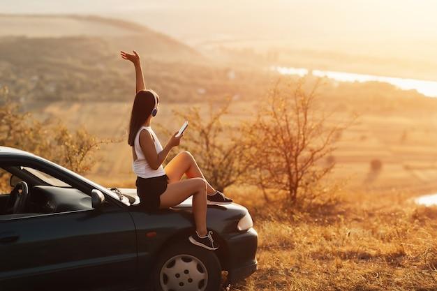 Giovane bella ragazza con la mano in alto, in cuffia ascoltando musica e cantando seduto sul cofano di un'auto al tramonto.