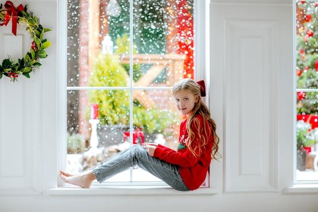 Giovane bella ragazza con lunghi capelli ricci biondi con fiocco rosso di natale e maglione invernale seduto sulla grande finestra con sfondo nevoso.