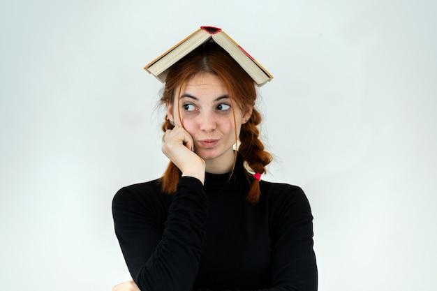 Giovane ragazza carina con un libro aperto in testa. concetto di lettura ed educazione.