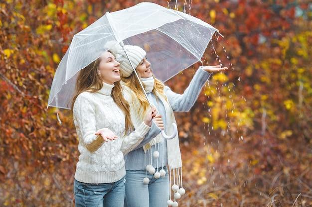 Giovani ragazze graziose divertendosi all'aperto in autunno. amici allegri in autunno