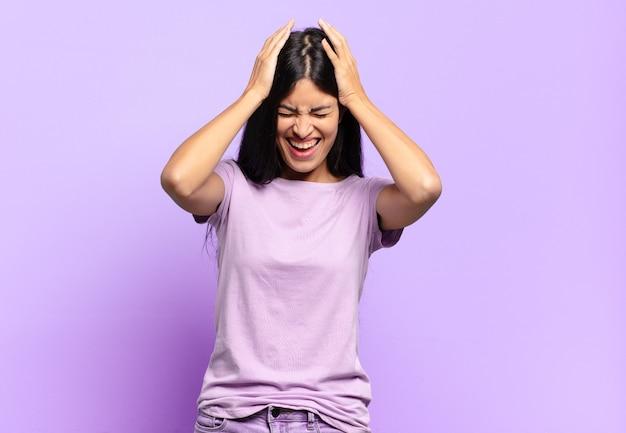 Giovane bella donna ispanica che si sente stressata e frustrata, alza le mani alla testa, si sente stanca, infelice e con emicrania