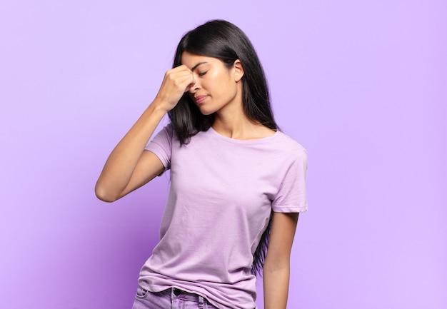 Giovane bella donna ispanica che si sente stressata, infelice e frustrata, tocca la fronte e soffre di emicrania di forte mal di testa