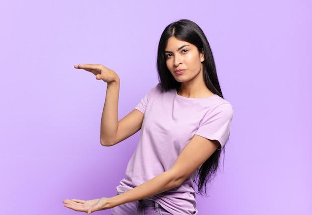 Giovane donna ispanica graziosa che tiene un oggetto con entrambe le mani sullo spazio della copia laterale, mostrando, offrendo o pubblicizzando un oggetto