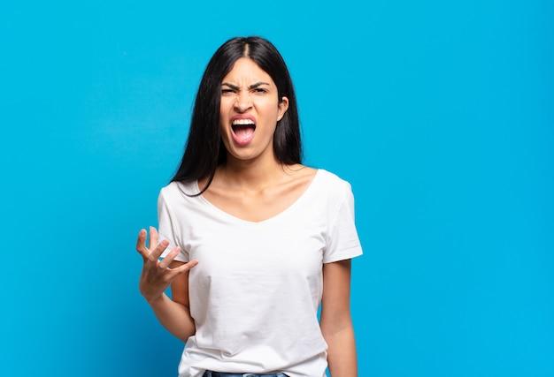 Giovane bella donna ispanica che sembra arrabbiata, infastidita e frustrata che urla wtf