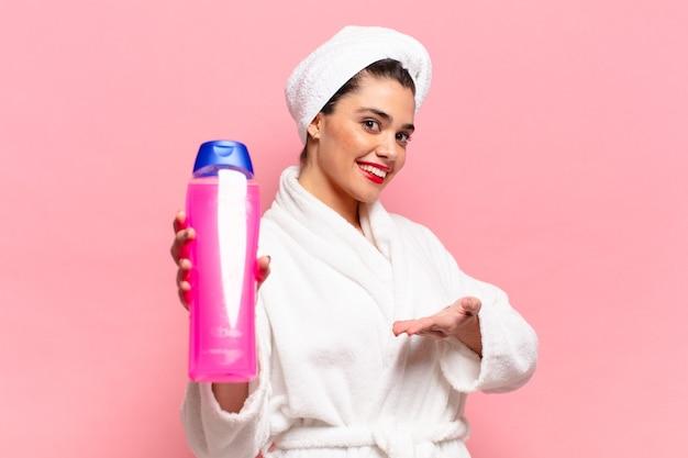 Giovane bella donna ispanica che mostra la bottiglia di shampoo