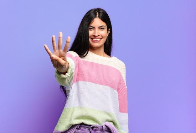 Giovane donna ispanica graziosa che sorride e che sembra amichevole, mostrando il numero quattro o quarto con la mano in avanti, conto alla rovescia