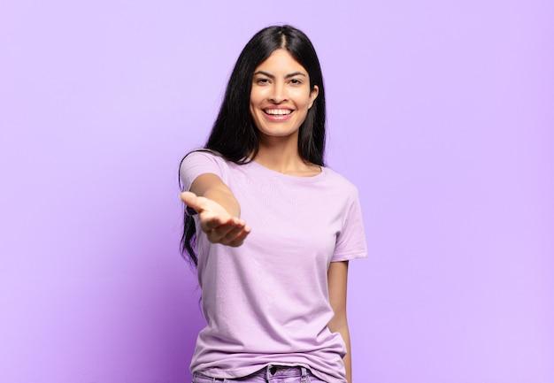 Giovane donna piuttosto ispanica che sorride, sembra felice, fiduciosa e amichevole, offrendo una stretta di mano per concludere un affare, collaborando