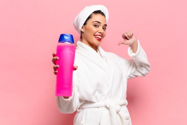 Giovane bella donna ispanica con un'espressione orgogliosa e felice che mostra una bottiglia di shampoo