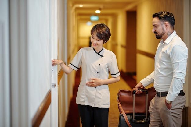 Giovane direttore d'albergo carino in uniforme che spiega agli ospiti come aprire la porta della stanza con la chiave elettronica