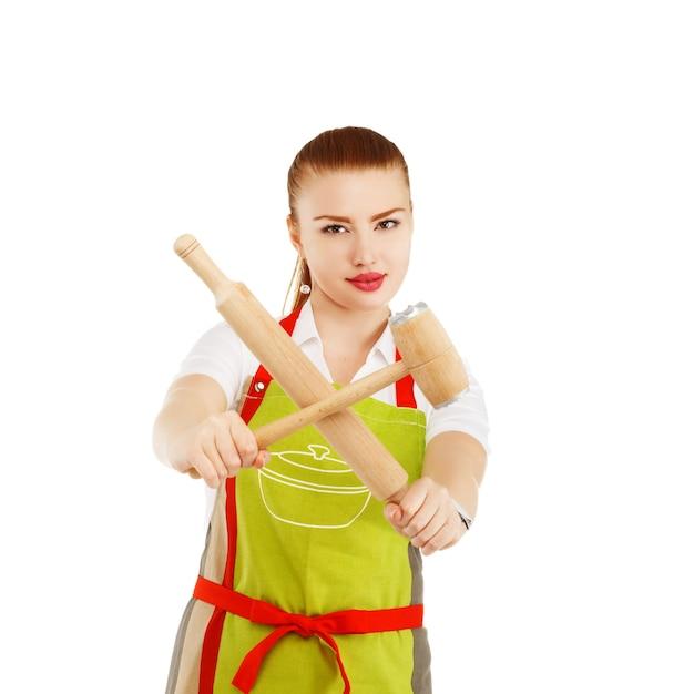 Giovane e graziosa casalinga con un mattarello e un martello di carne nelle sue mani