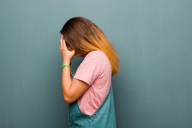 Giovane bella donna latina che copre gli occhi con le mani con uno sguardo triste e frustrato di disperazione, pianto, vista laterale contro il muro del grunge