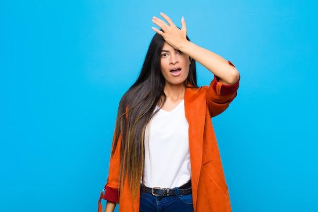 Giovane bella donna latina che alza il palmo alla fronte pensando oops, dopo aver commesso uno stupido errore o ricordando, sentendosi stupida contro il muro piatto