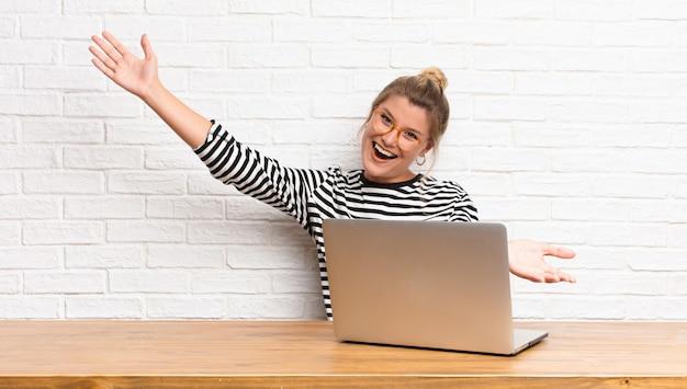 Giovane bella donna latina che sorride allegramente dando un caldo, amichevole, amorevole abbraccio di benvenuto, sentendosi felice e adorabile seduto con il suo laptop