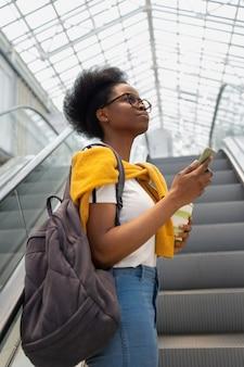 Giovane e graziosa donna millenaria su una scala mobile in un centro commerciale
