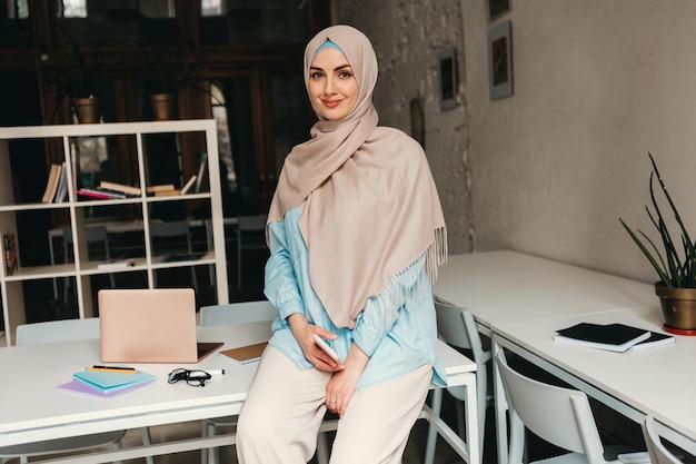 Giovane donna musulmana piuttosto moderna in hijab che lavora nella stanza dell'ufficio, istruzione online
