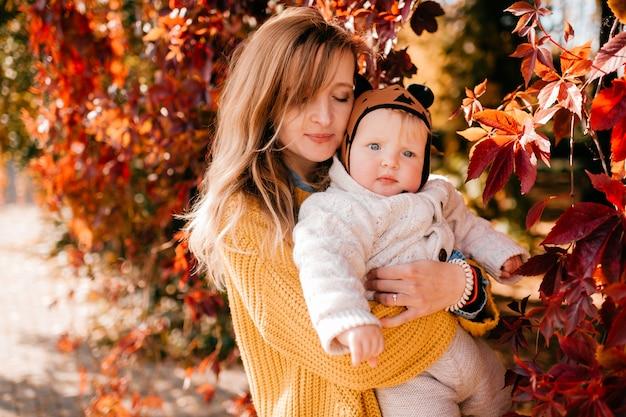 Giovane bella madre gode di trascorrere del tempo nel parco in autunno con il suo bambino piccolo