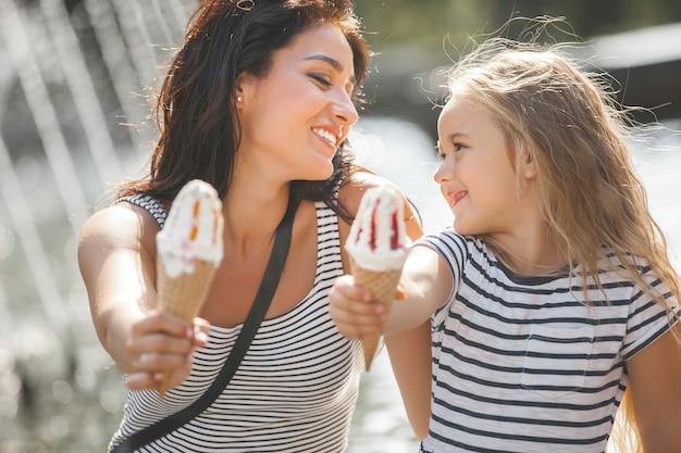 Giovane bella madre e sua figlia divertirsi insieme vicino alla fontana. bella donna e il suo bambino piccolo che mangia il gelato. famiglia allegra che si diverte.
