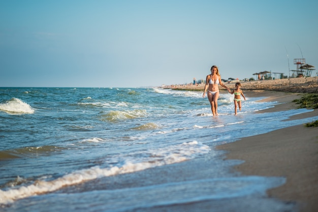 Giovane bella madre e figlia piccola corrono in riva al mare durante le vacanze in una soleggiata giornata estiva calda contro un cielo blu