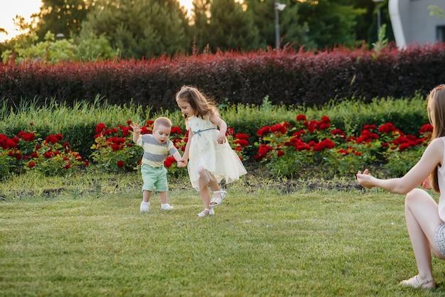 Una giovane graziosa madre con la figlia aiuta e insegna al figlioletto a muovere i primi passi durante il tramonto nel parco sull'erba.