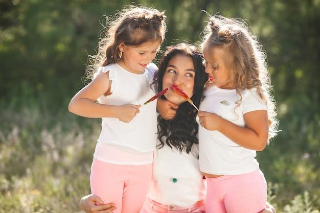 Giovane bella madre con le sue piccole figlie carina