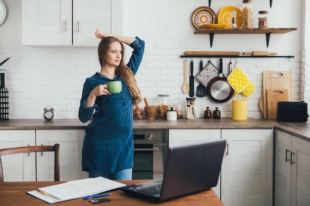 Giovane e graziosa ragazza freelance incinta lavora a casa in cucina in modalità di autoisolamento in quarantena e fa un riscaldamento dalla fatica