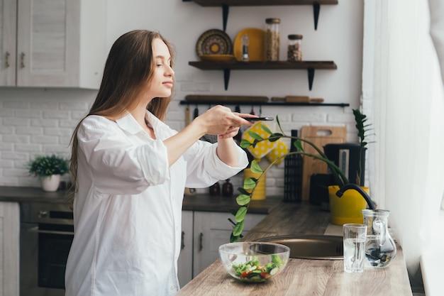 La giovane ragazza incinta graziosa scatta foto di un'insalata preparata sul suo smartphone