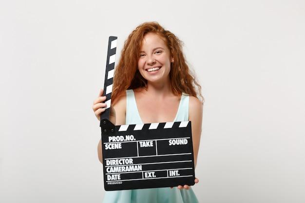 Ragazza di donna giovane bella rossa in abiti casual leggeri in posa isolato su sfondo bianco in studio. concetto di stile di vita della gente. mock up copia spazio. tenendo il classico ciak nero per la produzione di film.