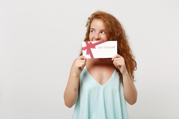Ragazza giovane bella donna dai capelli rossi in abiti casual leggeri in posa isolata sul fondo bianco della parete. concetto di stile di vita della gente. mock up copia spazio. coprendo la bocca con un buono regalo, guardando da parte.