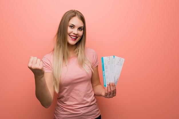 Giovane ragazza abbastanza russa sorpresa e scioccata. ha in mano un biglietto aereo.