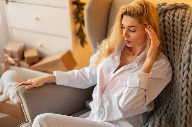 La giovane ragazza bionda abbastanza sexy in una camicia alla moda bianca si siede e riposa in poltrona con un plaid lavorato a maglia. vacanze di natale a casa