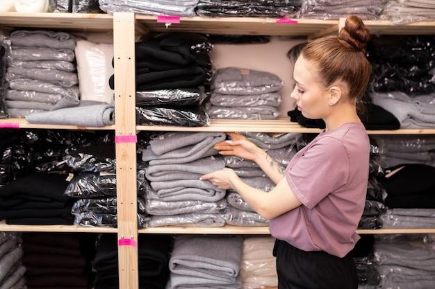 Giovane bella commessa che conta nuovi maglioni piegati imballati mentre si trova in piedi accanto a grandi scaffali con una pila di vestiti nel ripostiglio