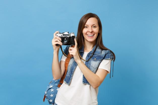 Giovane studentessa abbastanza sorridente in t-shirt bianca, vestiti in denim con zaino che tiene retro macchina fotografica vintage isolata su sfondo blu. istruzione al liceo. copia spazio per la pubblicità.