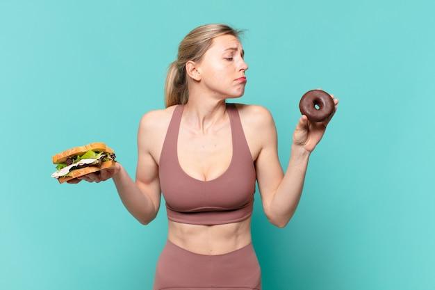 Giovane bella donna sportiva che dubita o ha un'espressione incerta e tiene in mano un panino e una ciambella