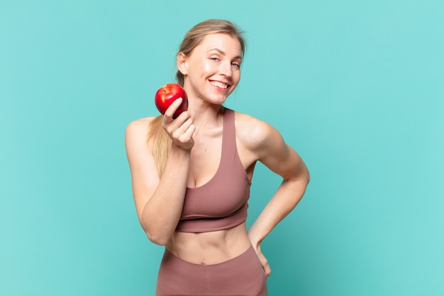 Espressione felice della giovane donna graziosa di sport e che tiene una mela